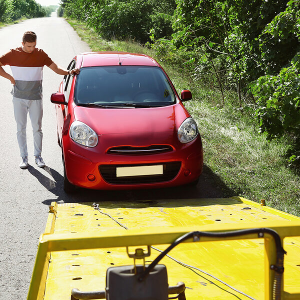man towing his car